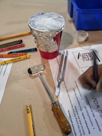 she made sand vibrate on the foil with a tuning fork and  mallet.